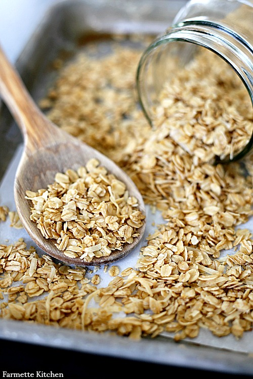 granola spilling out of a jar onto a wooden spoon and baking sheet