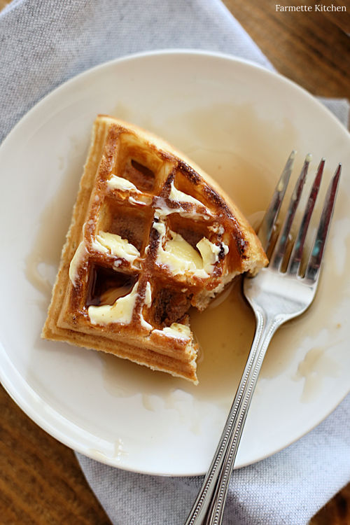 waffle with the corner gone on a plate with a fork