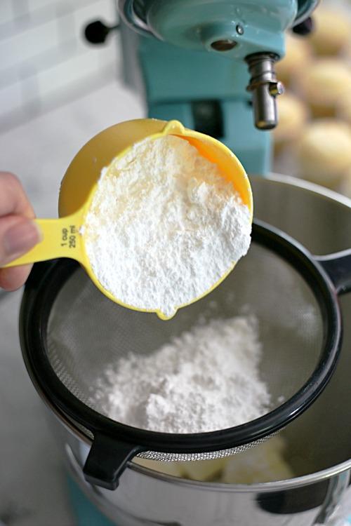 sifting powdered sugar into a mixing bowl