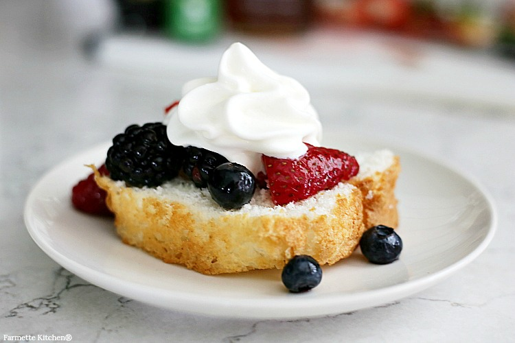 fresh fruit salad with berries and whipped cream spooned over Old Fashioned Pound Cake