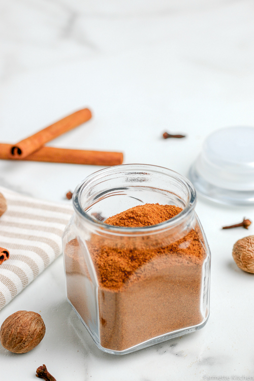 pumpkin pie spices in a jar next to a tan and white striped towel