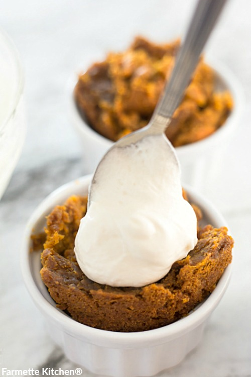 topping pumpkin cake with a big spoonful of cream cheese frosting