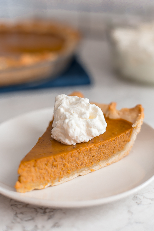 a piece of pumpkin pie with a big dollop of whipped cream