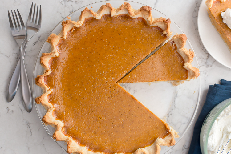 Pumpkin pie with a slice cut out and one slice removed