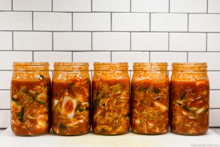 jars of kimchi lined up against a tile wall