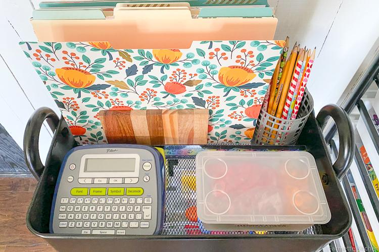 folders, label maker, and pencils on a shelf cart