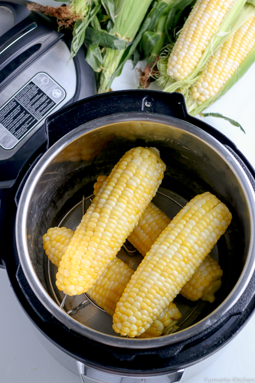 four ears of cooked corn in a pressure cooker