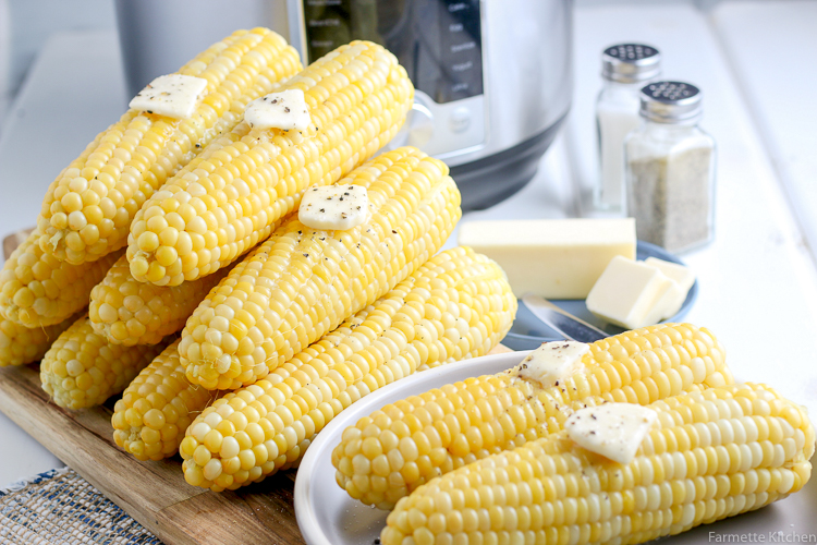 a stack of corn in front of a pressure cooker