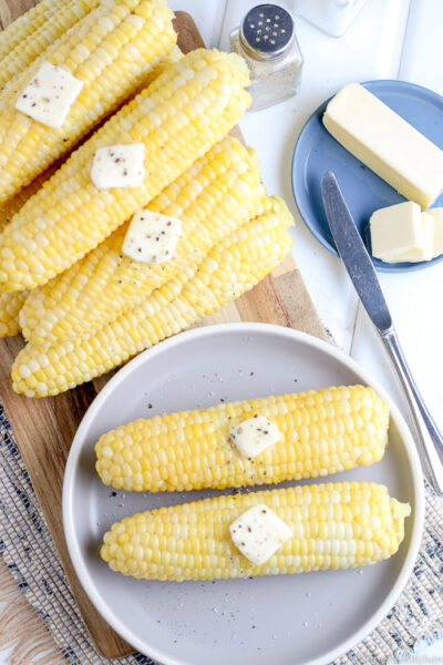 two ears of corn on a blue plate