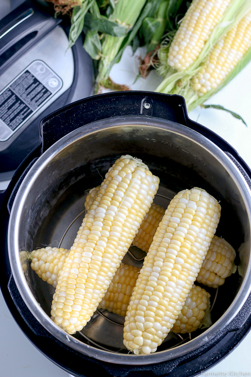 four ears of uncooked corn in a pressure cooker