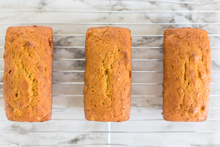 three mini loaves of pumpkin banana bread cooling on a wire rack