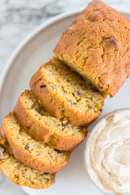 a loaf of pumpkin banana bread sliced next to a bowl of butter