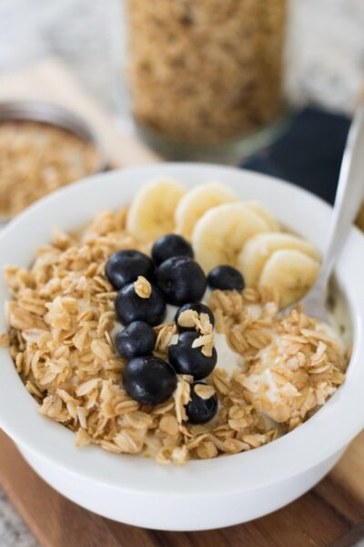 bowl of yogurt topped with granola, blueberries, and banana slices