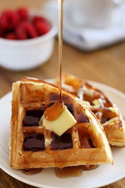 waffle on a plate with butter and syrup