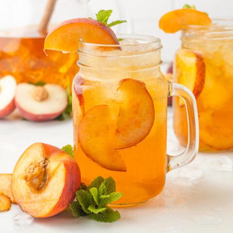 mason jar glasses with peach tea and slices of peaches