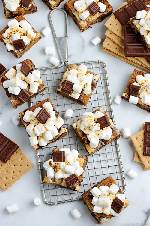smores bars on a wire rack with ingredients scattered around