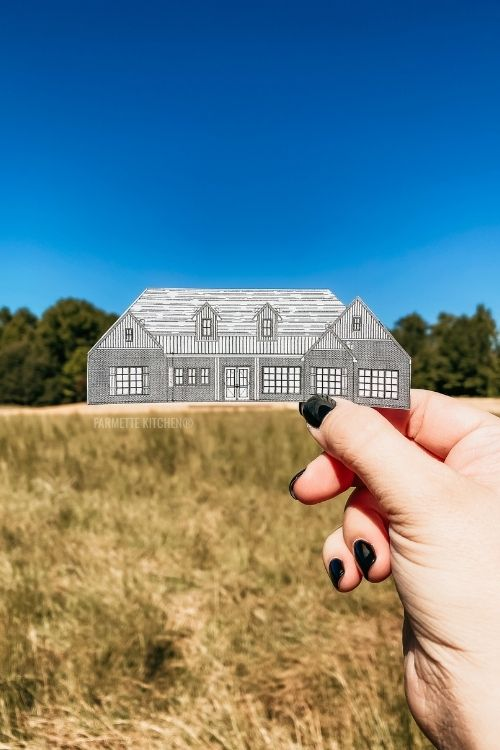 hand holding a cutout of a house